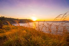 Rocky sea beach sunrise blue sky with grass. Phuket Thailand Stock Images