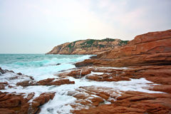 Rocky sea coast and blurred water in shek o Stock Photos