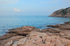 Rocky sea coast and blurred water in shek o Stock Images