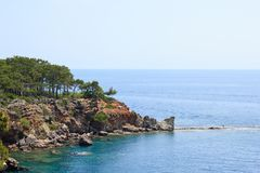 Rocky sea coast covered by pines in Kemer, Antalya, Turkey. Rocky Mediterranean sea coast covered by pines in Kemer, Antalya, Turkey stock photos