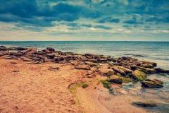 Rocky Baltic Sea coast. Deserted beach. Rocky sea coast with dramatic cloudy sky stock photo