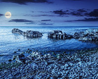 Rocky sea coast with seaweed at night Stock Photos