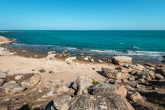 Rocky sea coast with turquoise water on beach royalty free stock images