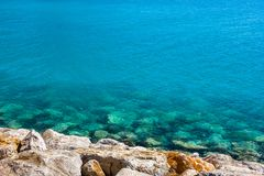 Rocky sea coast and turquoise water on a clear day stock image