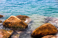 The rocky sea coast and water waves Stock Image