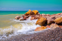 Rocky sea coast. The wave rolled on rocky shore Stock Image