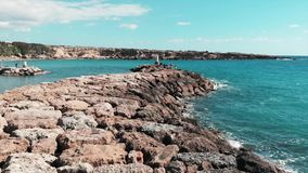 Rocky sea pier with ocean waves hitting cliffs creating white foam and water splashing. Aerial view of mediterranean sea coral bay. Rocky pier on windy sunny stock video footage