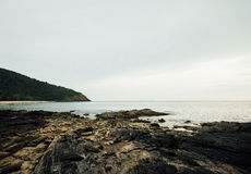 Rocky sea shore against a cloudy sky. Green hill on background cloudy sky Royalty Free Stock Photo