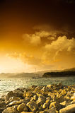 Rocky sea shore and dramatic sky at sunset Royalty Free Stock Photography