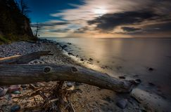 Rocky sea shore with driftwood at sunrise. Beautiful seascape Stock Photography