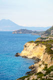 Rocky sea shore at ionian sea and mountain view in background Stock Photos