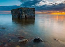 Rocky sea shore with old bunker in sea, long exposure photo Stock Photo