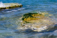 Rocky sea shore with pebble beach, waves with foam. Rocky sea shore with pebble beach, transparent waves with foam, on a warm summer day stock images