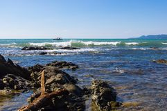 Rocky sea shore with pebble beach, waves with foam Royalty Free Stock Photography