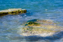 Rocky sea shore with pebble beach, waves with foam. Rocky sea shore with pebble beach, transparent waves with foam, on a warm summer day royalty free stock photography