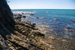 Rocky sea shore with pebble beach, waves with foam. Rocky sea shore with pebble beach, transparent waves with foam, on a warm summer day stock photography