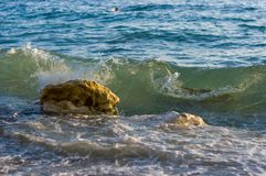 Rocky sea shore with pebble beach, waves with foam. Rocky sea shore with pebble beach, transparent waves with foam, on a warm summer day stock photo