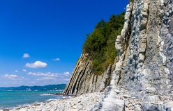 Rocky sea shore with pebble beach, waves with foam. Rocky sea shore with pebble beach, transparent waves with foam, on a warm summer day royalty free stock photo
