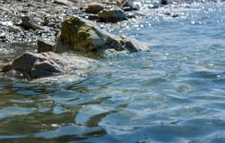Rocky sea shore with pebble beach, waves with foam. Rocky sea shore with pebble beach, transparent waves with foam, on a warm summer day stock image