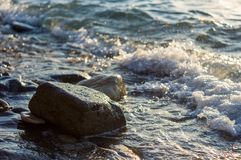 Rocky sea shore with pebble beach, waves with foam. Rocky sea shore with pebble beach, transparent waves with foam, on a warm summer day stock photos