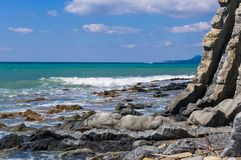 Rocky sea shore with pebble beach, waves with foam. Rocky sea shore with pebble beach, transparent waves with foam, on a warm summer day royalty free stock photos