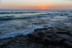 Rocky sea shore in rays of sunset sky. Wave beats on sea shore. Caspian Sea Kazakhstan royalty free stock image