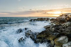 Rocky sea shore on sunset. Waves breaking against the rocks on the shore of Mallorca island, Spain Royalty Free Stock Image