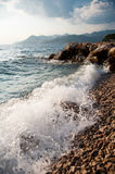 Rocky sea shore and waves splashing Stock Image
