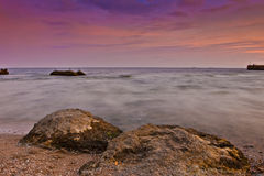 Rocky seacoast. At sunset time Stock Photos