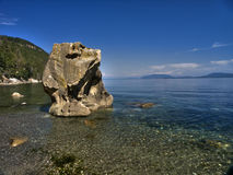 Rocky Seascape. A huge boulder stranded on a beach in the Pacific Ocean in southern British Columbia Stock Image