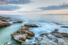 Rocky Seascape Sunset. This is a long exposure HDR photo of a rocky coastal travel seascape. This was taken at Beavertail State Park in Jamestown, Rhode Island Royalty Free Stock Photography
