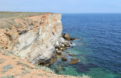 Rocky seashore. Beautiful seashore with high cliffs, waves batter against stones Stock Image