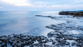 Rocky seashore and calm blue ocean Royalty Free Stock Images
