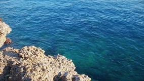 Rocky seashore with clear blue water stock video
