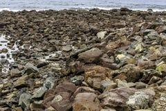 Rocky Seashore mit Oberteilen und Ozean lizenzfreie stockfotografie