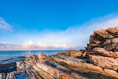 Rocky seashore in morning sunrise with bright blue sky and clouds Stock Photo