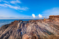 Rocky seashore in morning sunrise with bright blue sky and clouds Royalty Free Stock Photography
