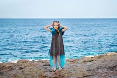 On a rocky seashore young girl princess skyblue dress like a bird queen puts on a crown stock images