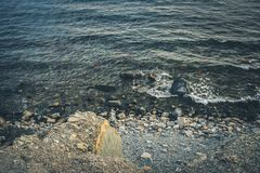 Rocky seashore with a quiet surf. Toned image. Rocky seashore with a quiet surf. Toned grey image. Selective focus Royalty Free Stock Photo