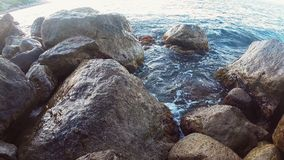 Rocky seashore and sea water splashing between the stones. Hd stock video