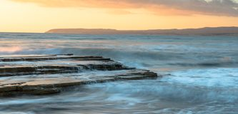 Rocky seashore seascape with wavy ocean during sunset. Rocky seashore seascape with wavy ocean and waves crashing on the rocks during a dramatic and beautiful Stock Images