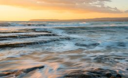 Rocky seashore seascape with wavy ocean during sunset. Rocky seashore seascape with wavy ocean and waves crashing on the rocks during a dramatic and beautiful Stock Image
