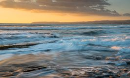 Rocky seashore seascape with wavy ocean during sunset. Rocky seashore seascape with wavy ocean and waves crashing on the rocks during a dramatic and beautiful Royalty Free Stock Photo