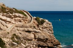 Rocky seashore. Stone staircase on the mountainside. Picturesque sea landscape. Summer seascape. Spain Stock Photo
