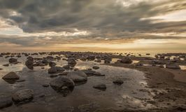 Peaceful sunset in the Gulf of Riga(Rīgas jūras līcis Vitrupē). Rocky Seashore at the Sunset of the Gulf of Riga(Rīgas jūras l stock image