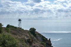 Rocky seashore view. With calm sea cloudy sky and watchtower on cliff Royalty Free Stock Photography
