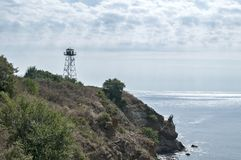 Rocky seashore view. With calm sea cloudy sky and watchtower on cliff Royalty Free Stock Photo