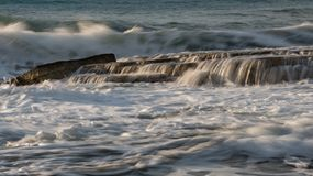Rocky seashore with wavy ocean and waves crashing on the rocks stock images