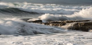 Rocky seashore with wavy ocean and waves crashing on the rocks royalty free stock image