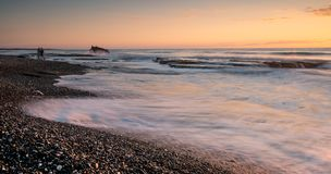 Rocky seashore with wavy ocean and waves crashing on the rocks. At Akrotiri coast area in Limassol, Cyprus royalty free stock photo